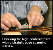 Checking for high-centered frets with a straight edge spanning 3 frets.